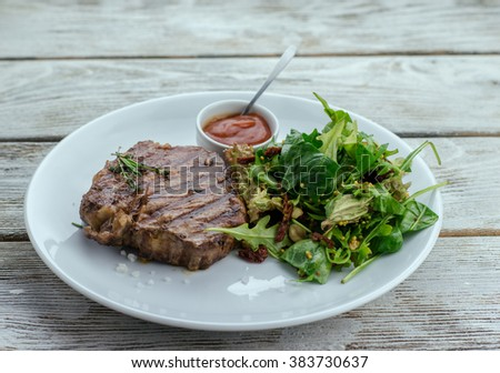 on the wooden table white plate with steak and arugula