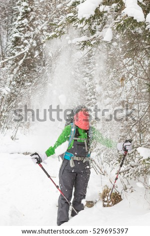 On Woman pours a lot of snow from tree.
