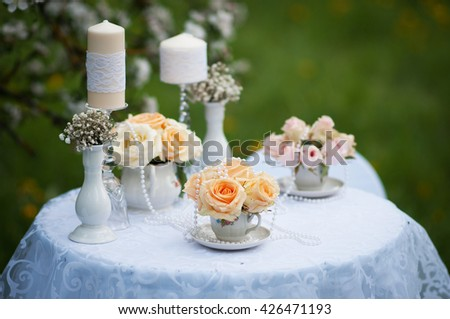 One beautiful fresh little decorative flower bouquet of orange and white roses standing in glass vase on wooden table outdoor on natural background, horizontal picture