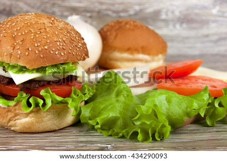 One beautiful juicy hamburger on a wooden table