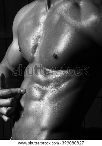 One beautiful sensual male athletic bare body with muscular chest strong abdomen with wet skin pointing to attractive cool six-packs studio black and white closeup