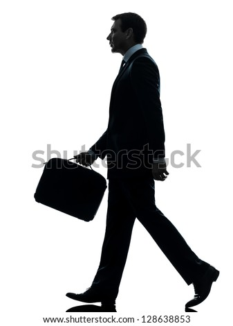 one caucasian businessman walking side view in silhouette studio isolated on white background