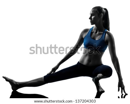 one caucasian woman exercising yoga stretching legs warm up in silhouette studio isolated on white background