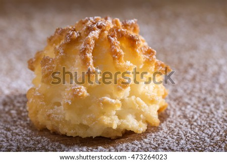 One coconut macaroons christmas cookies with powdered sugar on wooden background
