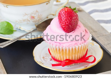 one cupcake with fresh strawberry in plate on wooden table