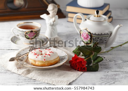 One donut on valentine day on plate with cup of tea