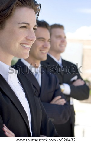 one female two males wearing dark business suits in a row smiling