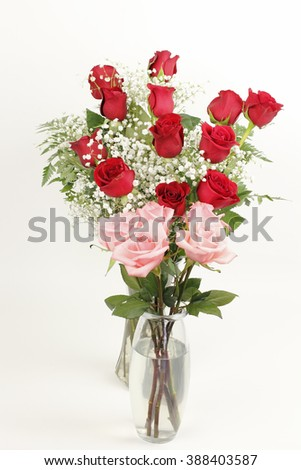 One glass vase bouquet of pink roses  in front of a glass vase of red rose s floral arrangement in front of an off white background. Two pretty rose bouquets in glass vases.