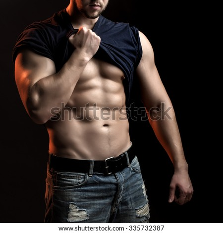 One handsome sexual strong young man with muscular body in blue jeans with shirt on shoulder standing posing in studio on black background, square picture
