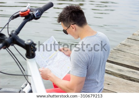 One happy tourist bicyclist with route map