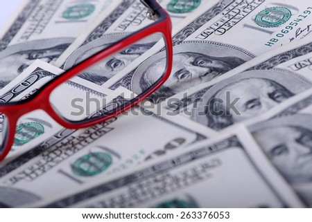 One hundred dollars banknotes as a background and glasses