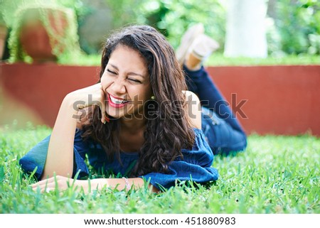 one laughing young latino girl on grass in park