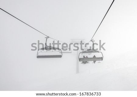 One of chair lifts in a ski resort of a valley of Zillertal in the haze - Mayrhofen region, Austria