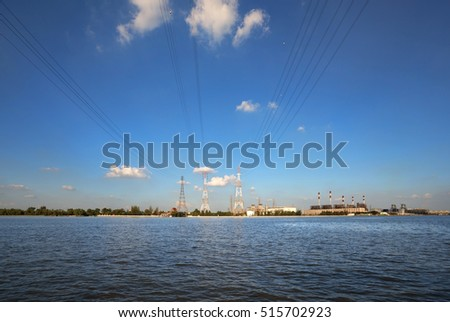 One of Power station and high voltage power lines at Chao Phraya river side, Bangkok, Thailand.(With warm sunlight effect in the evening )