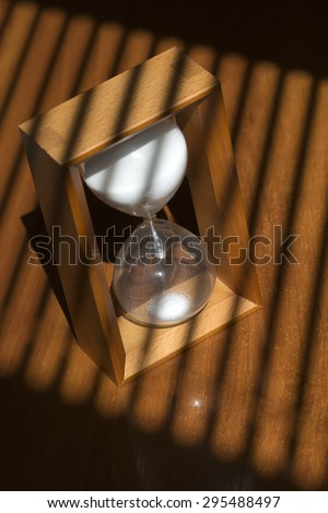 One old fashiouned wooden hour glass clock with white sand standing on table top in jalousie shade, vertical picture