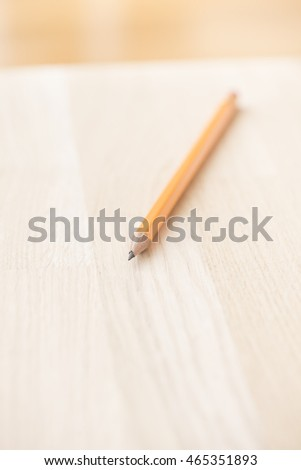 One pencil lying on wood table. Concept of writing, education and communication. Copyspace.