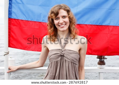 One Russian beautiful young female standing under flag of Russia