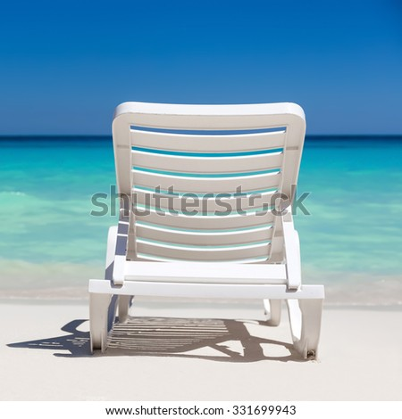 One sunbed on tropical calm beach with turquoise caribbean sea water and white sand