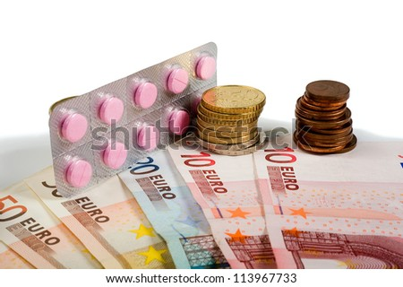 One tablet with pills between paper money and euro coins