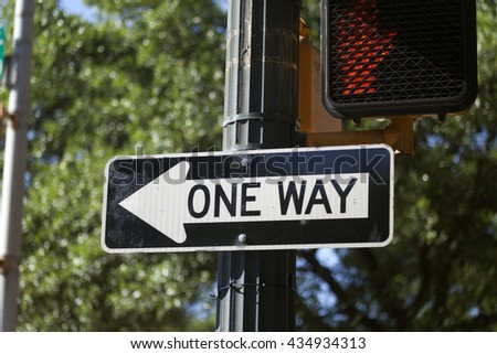 One Way sign next to a traffic light with tress in the background