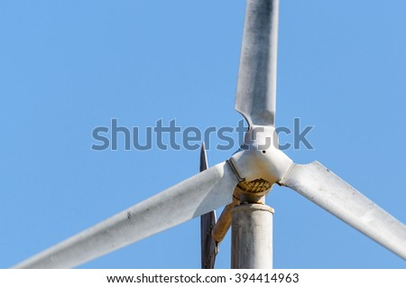 One white wind turbine and blurred blade on blue sky background.