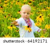 One year boy in folk shirt staying in the field of yellow flowers - stock photo