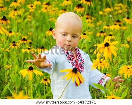 One year boy in folk shirt staying in the field of yellow flowers
