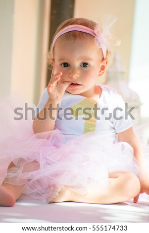 One year old baby girl celebrating her first birthday wearing a personalized 1 year old t-shirt and a tutu