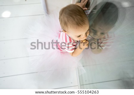 One year old baby girl is reflected in the glass of a window
