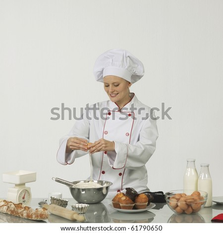 One young woman professional cook. She is braking an egg into a bowl of flour