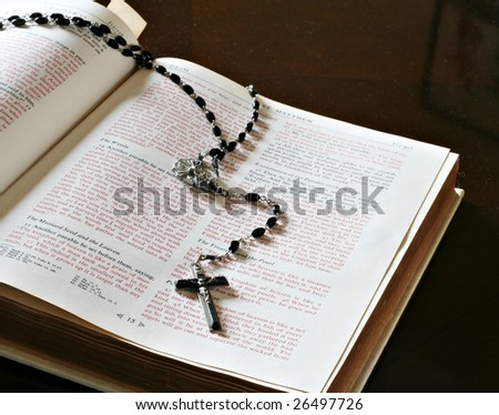 Open bible with black cross and rosary