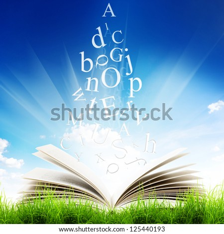 Open book with flying letters in green grass over blue sky background. Magic book