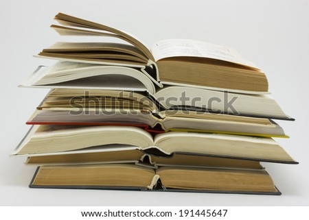 Open books are stacked to read text