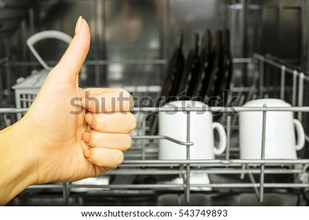 Open dishwasher with clean utensils in it, woman hands loading dishes to the dishwasher machine, introducing or taking out a plate and cup, clean tableware after cleaning process