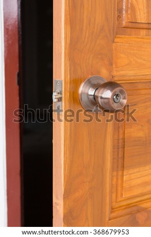 open door, door knob and keyhole on wooden door, close up image