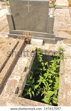 open overgrown and lonely grave stock photo
