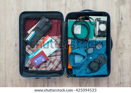 Open traveler's bag with clothing, accessories, credit card, tickets and passport, travel and vacations concept