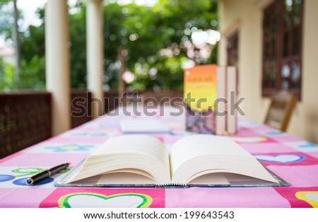opened book on the table with pen and blur background