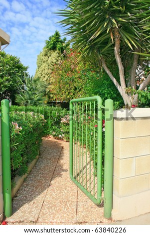 Opened green gate at the house.