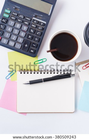 Opened notebook with blank space for text or message, sticky paper, calculator, and take away coffee cup on office table