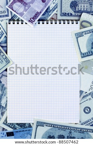 Opened spiral notepad (notebook) sheet in a cage on money background ( euro and dollars cash).  stained blue.