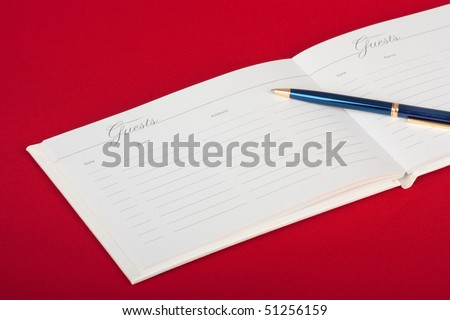 Opened wedding guest book with a pen on a red background