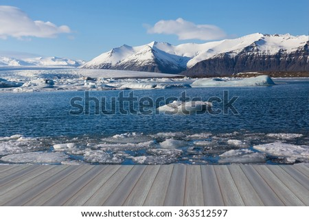 Opening wooden floor, Jojulsarion glacial and lake with snow covered mountain background in winter of Iceland