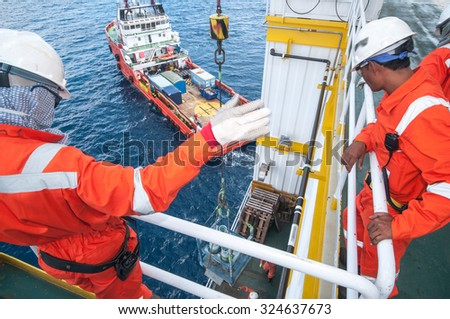 operator workers on offshore rig. loading bulk ship. heavy industrial. logistic.