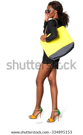 Optimistic African woman with dark brown hair in beach outfit holding purse - Isolated