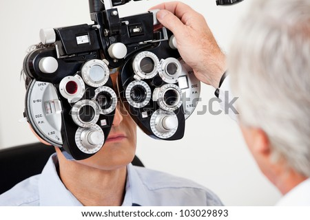 Optometrist performing eye test with phoropter on a male patient