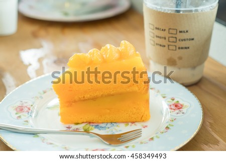Orange cake and cold coffee on wooden background
