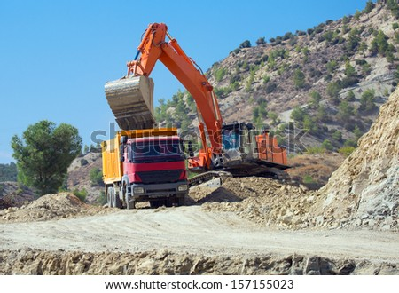 Orange excavator loading soil into a dumper truck on construction site