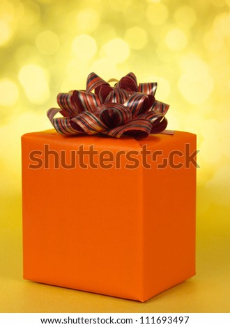 orange gift box with assorted bow, yellow background