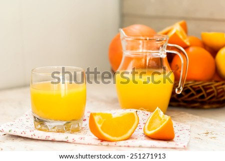 orange juice in a glass and slices of orange on the background basket with oranges and juice carafe